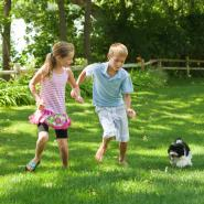 Two children playing outside with their small dog in a pest free yard.