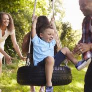 Family of four playing on a tire swing together
