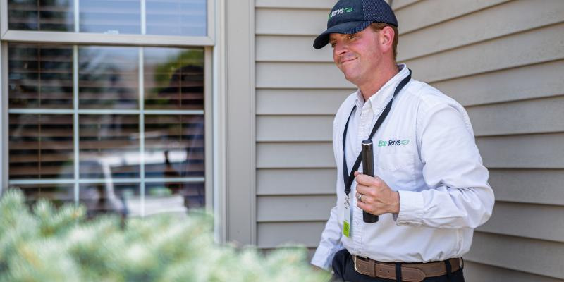 ecoservice technician checking property for mosquitoes and ticks