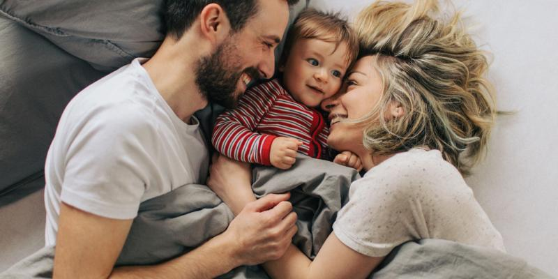 Father, mother, and child laying in a bed with gray sheets.