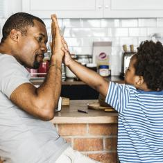 father and son high-fiving in kitchen with mom
